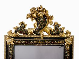 "PAIR OF MIRRORS, VENICE, SECOND QUARTER OF THE 18TH CENTURYPAIR OF MIRRORS, VENICE, SECOND QUARTER OF THE 18TH CENTURY  in ebonized, lacquered and gilded wood with mother of pearl marquetry and foliage in sculpted and gilded wood, 168x98 cm  This pair of frames is a typical and refined expression of the early rococo atmosphere in Venice during the second quarter of the 18th century. This was a moment in time in which the gilded mirror passed from being mostly used for private grooming to constituting a furnishing element in its own right, over a progressive process of emancipation. During this still transitory phase, during which each city exhibited its own decorative techniques, Venice became one of the main protagonists, laying the foundation for a decorative style that will constitute a key influence for the coming decades.  Over the course of the 18th century, the creation of these artefacts is so deeply rooted in the venetian lagoon that within the guild of the marangoni, or woodworkers, there developed a specific branch of highly specialized master carvers, the marangoni de soaza. At the same time, there was a multiplication of workshops managed by soaza artisans: 36 workshops with 94 masters, 124 workers and 24 helpers according to a 1773 statistic polled by the magistrates and trade regulators of the Savi della Mercanzia. The venetian masters did not shy away from letting their creativity run loose, using an ornamentation technique at which they excelled, enamelling, in which the decoration, drawn on a monochrome stucco base is then polished with a layer of varnish, called sandracca. It was in this way that the same kinds of ornamentations which decorated chests and other furnishings went on to embellish mirror-frames, animating them with exotic themes, or chinoiserie. A particular predilection is reserved for decorations modelled after flowers and of oriental inspiration which, drawn vividly and with narrative gusto, stand out with their rich colours against the neutral, often dark backgrounds, alternated with branches and leaves and creating an exuberant but at the same time composedly elegant picture. When a given commission is particularly important, these decorations may also be further enriched by evocative pearl inlays, as with the red and gold lacquered wood frame made in Venice at the end of the 17th century and currently held in the Gemäldegalerie in Berlin (fig. 1), or the one probably dating from the early 18th century and held in a private collection (fig. 2). It is also the case of our two frames, which were probably requested by an important family for a significant occasion. The combination of lacquer and pearl was a venetian prerogative between the late 17th and early 18th centuries. Many carvers produced this kind of decoration, among whom we must mention the architect, engraver, carver, and inlayer Domenico Rossetti, famous for his ""works with pearl and in the Chinese style"".  This pictorial richness was paralleled by an equal sculptural vivacity, which expressed itself – as well as in the creation of frames in a wide array of styles and shapes – in adding further elements of carved wood to the frames. Additions in sculpted and gilded wood are often attached to the four outer corners of the frame. We can see this in our pair's ogival motif, creating a kind of counter-frame which was supposed to make the mirror stand out against the wall. But a greater importance is without doubt given to the coping, a necessary crowning of the upper part of the mirror. In the carving of this component, the venetian masters let their creative imagination run wild, showing off their whole repertory of leaves, shells, festoons, and, as in the present case, cartouches, often made so that they would hold a family crest or, as is the case here, decorated with the same pictorial motifs embellished with pearl that are found on the main body of the frame.  Almost as if replying to the painted floral motifs, the coping is populated by elements in painted and carved wood, made with a mastery fully on par with that of the expert and imaginative master painters. In our mirror-frames, flower and fruit alternated with leafy folds frame the central coping, the asymmetrical position of which creates a decentred effect typical of the 18th century, whilst the four corners of the frames are marked – symmetrically this time – by small sculpted and polished folders in the middle of the pearl component. And whilst often in this kind of mirror-frame the sculptural element tends to dominate over the pictorial one, concentrating the focal point of attention on the coping, here the overall composition is characterized by a marked equilibrium, in which all elements, both sculptural and pictorial, cohabit and form a harmonious whole.  In this sense, these mirror-frames can be fully included in early rococo production, when the festive and daring baroque evolved into lines which – whilst still dominated by an inventive force and capricious exuberance – reflected the period's more graceful and refined taste. During these few years, many sculptors and woodcarvers place their art in the service of frame-making, including Antonio Gai, Antonio Corradini, or Andrea Brustolon, noted for having made multiple frames alongside the furnishings for the Venier family, now held in Palazzo Rezzonico. Following his drawing, the luxurious throne for the church of the Gesuati in Venice was made in the early 18th century (fig. 3). Its precious pearl inlays, together with its folds and rich wooden sculpted and gilded flowers, constitute one of the first examples of a decorative taste which will exercise much influence over the following decades. Our mirror-frames, thus, may be included precisely in this current.   Comparative literature G. Mariacher, Specchiere italiane e cornici da specchio, dal XV al XIX secolo, Milan 1963, pp. 16-24; E. Colle, Il mobile barocco in Italia, Milan 2000, p. 332; C. Santini, Mille mobili veneti. L'arredo domestico in Veneto dal sec. XV al sec. XIX, III, Modena 2002, pp. 246-247 nn. 424-426                PAIR OF MIRRORS, VENICE, SECOND QUARTER OF THE 18TH CENTURY  in ebonized, lacquered and gilded wood with mother of pearl marquetry and foliage in sculpted and gilded wood, 168x98 cm  This pair of frames is a typical and refined expression of the early rococo atmosphere in Venice during the second quarter of the 18th century. This was a moment in time in which the gilded mirror passed from being mostly used for private grooming to constituting a furnishing element in its own right, over a progressive process of emancipation. During this still transitory phase, during which each city exhibited its own decorative techniques, Venice became one of the main protagonists, laying the foundation for a decorative style that will constitute a key influence for the coming decades.  Over the course of the 18th century, the creation of these artefacts is so deeply rooted in the venetian lagoon that within the guild of the marangoni, or woodworkers, there developed a specific branch of highly specialized master carvers, the marangoni de soaza. At the same time, there was a multiplication of workshops managed by soaza artisans: 36 workshops with 94 masters, 124 workers and 24 helpers according to a 1773 statistic polled by the magistrates and trade regulators of the Savi della Mercanzia. The venetian masters did not shy away from letting their creativity run loose, using an ornamentation technique at which they excelled, enamelling, in which the decoration, drawn on a monochrome stucco base is then polished with a layer of varnish, called sandracca. It was in this way that the same kinds of ornamentations which decorated chests and other furnishings went on to embellish mirror-frames, animating them with exotic themes, or chinoiserie. A particular predilection is reserved for decorations modelled after flowers and of oriental inspiration which, drawn vividly and with narrative gusto, stand out with their rich colours against the neutral, often dark backgrounds, alternated with branches and leaves and creating an exuberant but at the same time composedly elegant picture. When a given commission is particularly important, these decorations may also be further enriched by evocative pearl inlays, as with the red and gold lacquered wood frame made in Venice at the end of the 17th century and currently held in the Gemäldegalerie in Berlin (fig. 1), or the one probably dating from the early 18th century and held in a private collection (fig. 2). It is also the case of our two frames, which were probably requested by an important family for a significant occasion. The combination of lacquer and pearl was a venetian prerogative between the late 17th and early 18th centuries. Many carvers produced this kind of decoration, among whom we must mention the architect, engraver, carver, and inlayer Domenico Rossetti, famous for his ""works with pearl and in the Chinese style"".  This pictorial richness was paralleled by an equal sculptural vivacity, which expressed itself – as well as in the creation of frames in a wide array of styles and shapes – in adding further elements of carved wood to the frames. Additions in sculpted and gilded wood are often attached to the four outer corners of the frame. We can see this in our pair's ogival motif, creating a kind of counter-frame which was supposed to make the mirror stand out against the wall. But a greater importance is without doubt given to the coping, a necessary crowning of the upper part of the mirror. In the carving of this component, the venetian masters let their creative imagination run wild, showing off their whole repertory of leaves, shells, festoons, and, as in the present case, cartouches, often made so that they would hold a family crest or, as is the case here, decorated with the same pictorial motifs embellished with pearl that are found on the main body of the frame.  Almost as if replying to the painted floral motifs, the coping is populated by elements in painted and carved wood, made with a mastery fully on par with that of the expert and imaginative master painters. In our mirror-frames, flower and fruit alternated with leafy folds frame the central coping, the asymmetrical position of which creates a decentred effect typical of the 18th century, whilst the four corners of the frames are marked – symmetrically this time – by small sculpted and polished folders in the middle of the pearl component. And whilst often in this kind of mirror-frame the sculptural element tends to dominate over the pictorial one, concentrating the focal point of attention on the coping, here the overall composition is characterized by a marked equilibrium, in which all elements, both sculptural and pictorial, cohabit and form a harmonious whole.  In this sense, these mirror-frames can be fully included in early rococo production, when the festive and daring baroque evolved into lines which – whilst still dominated by an inventive force and capricious exuberance – reflected the period's more graceful and refined taste. During these few years, many sculptors and woodcarvers place their art in the service of frame-making, including Antonio Gai, Antonio Corradini, or Andrea Brustolon, noted for having made multiple frames alongside the furnishings for the Venier family, now held in Palazzo Rezzonico. Following his drawing, the luxurious throne for the church of the Gesuati in Venice was made in the early 18th century (fig. 3). Its precious pearl inlays, together with its folds and rich wooden sculpted and gilded flowers, constitute one of the first examples of a decorative taste which will exercise much influence over the following decades. Our mirror-frames, thus, may be included precisely in this current.   Comparative literature G. Mariacher, Specchiere italiane e cornici da specchio, dal XV al XIX secolo, Milan 1963, pp. 16-24; E. Colle, Il mobile barocco in Italia, Milan 2000, p. 332; C. Santini, Mille mobili veneti. L'arredo domestico in Veneto dal sec. XV al sec. XIX, III, Modena 2002, pp. 246-247 nn. 424-426"